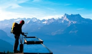 Hiker at a rest stop at a fountain high above Leysin in the region of les Diablerets, Canton of Vaud. In the background the massif of Dents du Midi, 3178 m high.